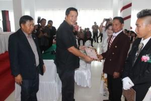 Steven Kandouw didampingi Bupati James Sumendap menyerahkan akteh nikah pada kegiatan nikah massal Pemkab Mitra