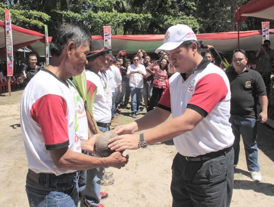 Wagub Sulut, Steven Kandouw, menyerahkan bantuan bibit kelapa kepada petani di acara pencanangan Gerakan Prima untuk ODSK