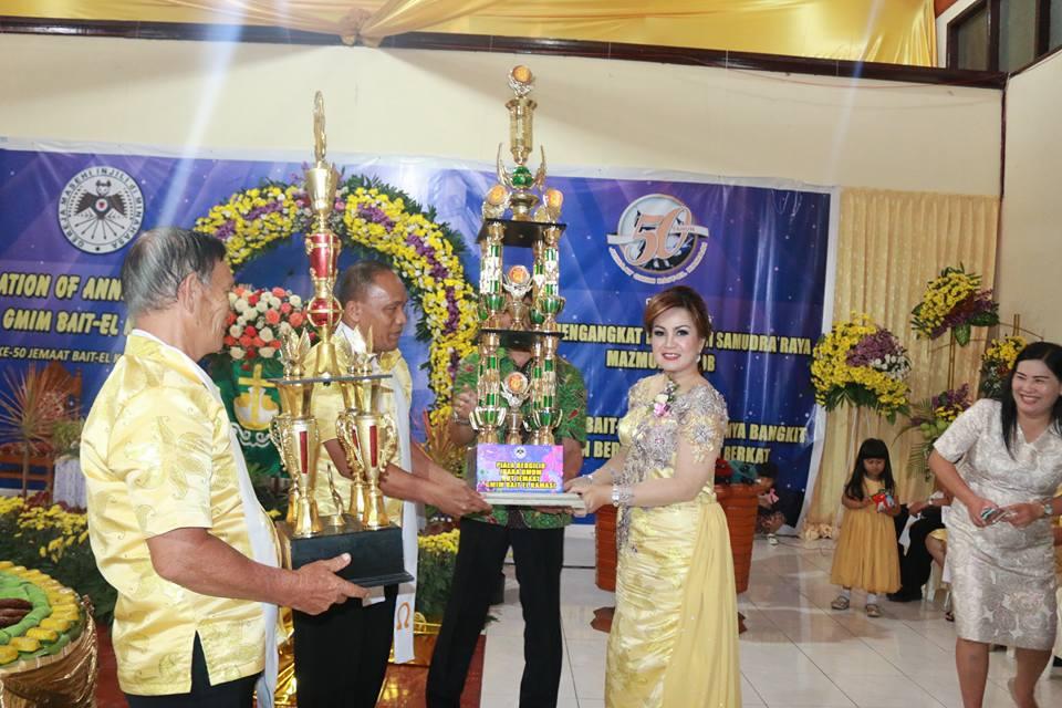 Ketua Umum Panitia, Syerly Adelyn Sompotan menyerahkan Piala Juara Umum kepada Kolom 10