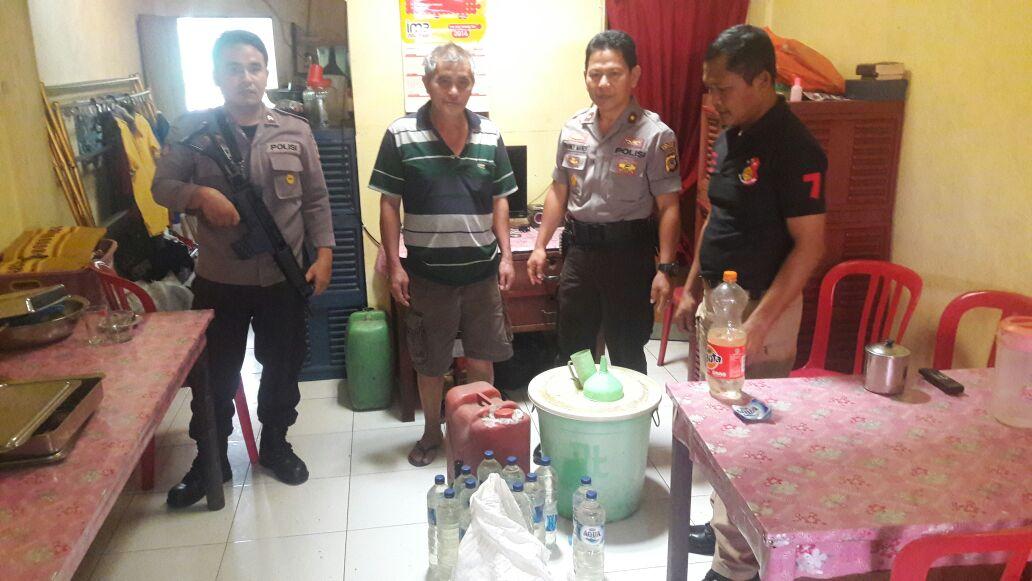 Polisi saat menyita minuman keras jenis cap tikus di Pasar Tomohon