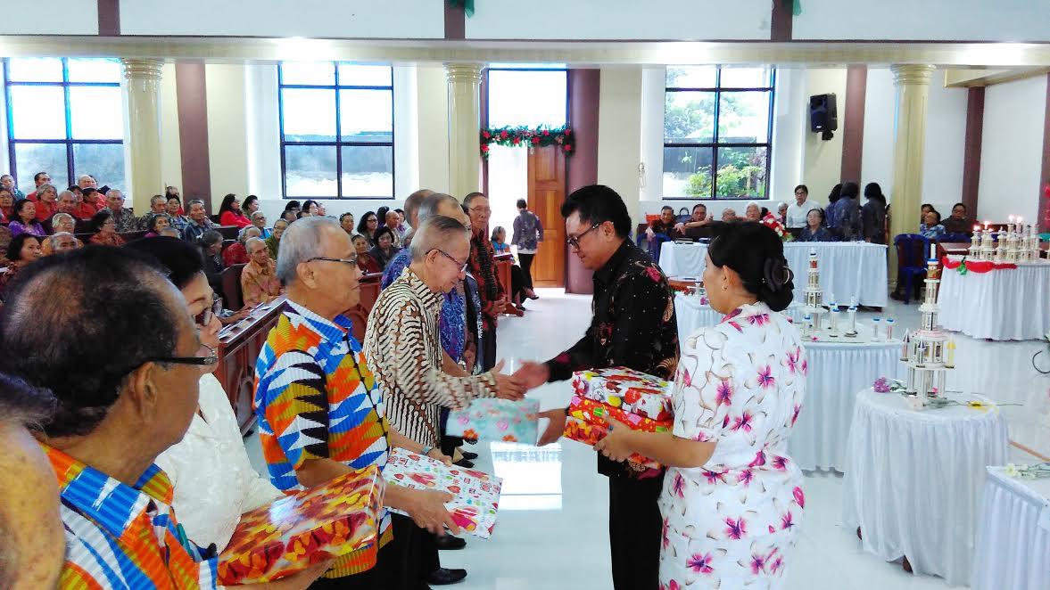 Ketua Panitia Ir Ervinz DH Liuw MSi membagikan bingkisan Natak kepada Lansia