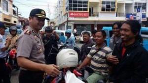 Kapolres Minsel saat bagi-bagi helm kepada warga