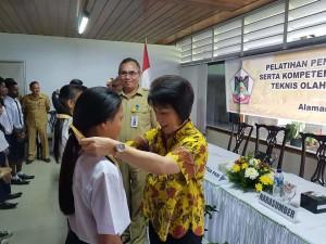 Ketua KONI Tomohon mengalungkan medali pemenang