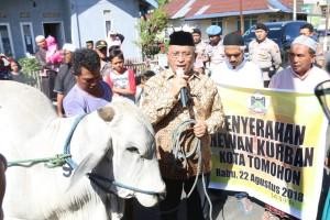 SEkretaris Kota Ir Harold V Lolowang MSc MTh menyerahkan kurban