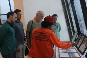 Pemandu sementara menjelaskan foto-foto yang terpampang kepada turis Jerman