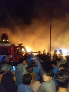 Petugas dan warga sekitar berusaha memadamkan api
