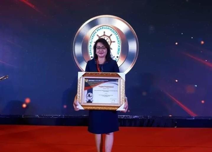 Sekretaris DPM-PTSP, Stefny Rengkung ketika menerima penghargaan